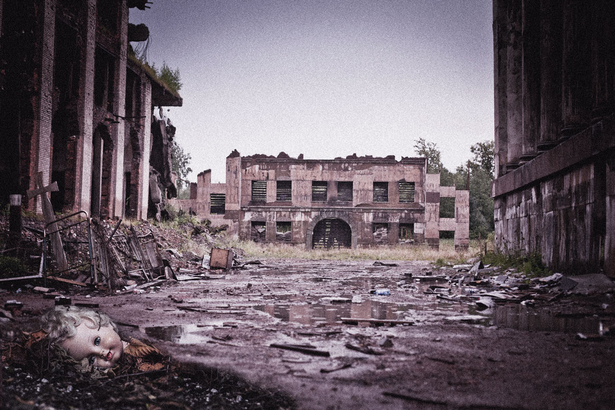 An indigo-tinged photo of a ruined factory floor, with a doll's head lying in the rubble in the foreground.